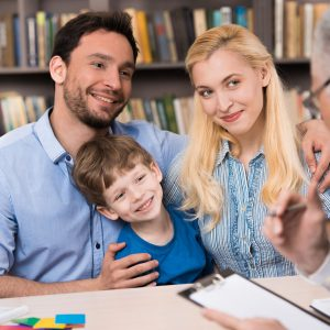 Foto de matrimonio con hijo feliz frente al psicologo